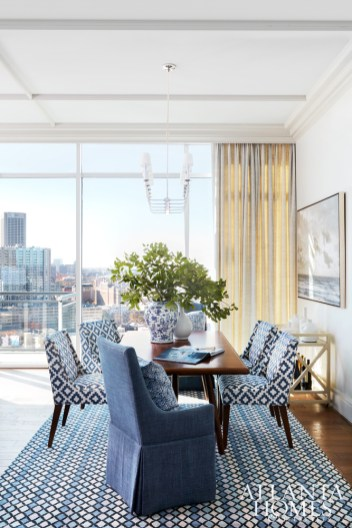 The horizontal light fixture in the dining room is hung higher than average so as not to block the view from the adjoining kitchen. Blue linen host chairs, Lee Industries. Chandelier, Visual Comfort.