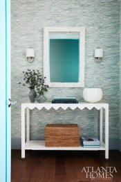 The foyer sets the tone for what's to come with its feathery blue-patterned Twigs wallpaper. Sconces, Urban Electric.