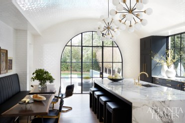 """Custom tile from SOURCE lines the kitchen walls and extends up to the barrel-vaulted ceiling. """"We actually have a tiled kitchen at our own house,"""" says Turner. """"We loved it so much that we wanted to incorporate it in this house."""" To make the room feel even more open, they avoided upper cabinetry. The black-and-white palette strikes a harmonious balance between masculine and feminine. Barstools, Bradley. Banquette, TecnoSedia. Appliances through Guy Gunter Home."""