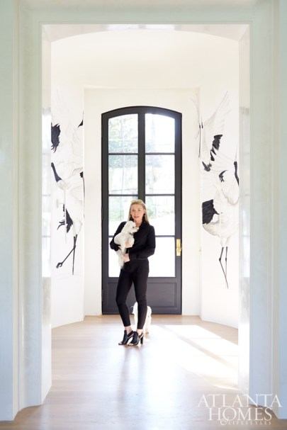 Melanie Turner and pup Scooter stand in the home's entryway, where a pair of crane murals by Bethany Travis create a unique welcome.