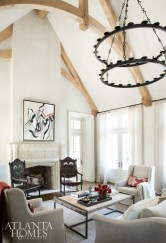 Just over the threshold, the kitchen's contained and cozy dimensions transition quickly to soaring heights, where the vaulted ceiling of the combination family and breakfast room features expertly crafted timber framing. Trestle table, Bungalow Classic. Dining chairs, Restoration Hardware.