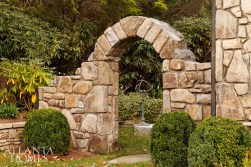 An arch in the garden frames an armillary, providing a focal point.