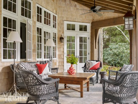 The loggia boasts a comfortable rustic air with the wicker chairs, wooden coffee table and beam detailing. A pair of floor lamps and Link outdoor fabrics matches the comfort-meets-sophisticated vibe from inside.