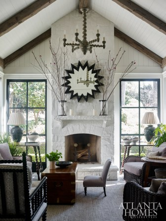 The stacked-stone fireplace was parged and painted white to brighten the space. With its integration into the interior of the house, the family can hang out and entertain here year-round. The mirror from B.D. Jeffries was made from an architectural element that was likely once used in a garden.
