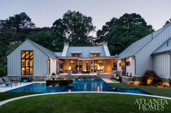 Classic board-and-batten is juxtaposed with modern metal details for a fresh farmhouse feel. The pool was designed by J. Brownlee Design of Nashville.