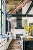 Cabinets crafted by Beni Borza of Kingdom Woodworks incorporate African mahogany and white cedar to add warmth to the streamlined kitchen. The stove hood and I-beams, originally raw steel, were given a patinated finish to add age and texture.