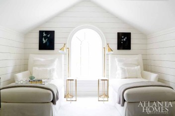 Originally an attic space, this newly built-out, third-floor guest suite adds sleeping quarters in the chicest of ways thanks to a pair of bunk niches on one end, and multifunctional chaise lounges in another. White shiplap adds dimension to the formerly dormant space and takes full advantage of the light streaming in from the arched window of the historic home's front facade.