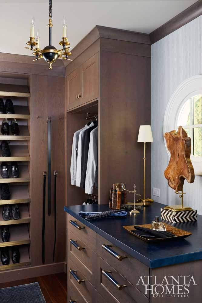 """Closets are all about the hardware, says Quinn, so masculine touches, from custom-designed hooks to the leather countertops, fill this gentleman's walk-in closet. Brass details were incorporated into the shoe shelves, and detailed hooks and brass hanging rods from Matthew Quinn Collection at ADAC West fill the handsome space. """"You start the day in your closet and end the day in your closet,"""" he says. """"It's the little things that make it feel special."""""""