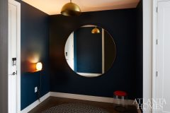 A wall painted Farrow & Ball's Hague Blue gives the entryway a moody energy.