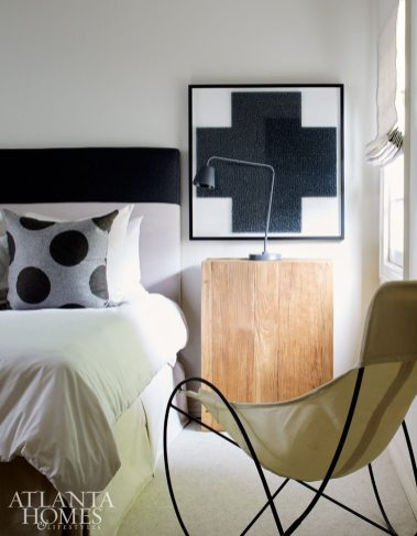 The custom headboard and linens by Kay Douglass Interiors capitalize on the monochromatic tone of the son's bedroom, where a framed gray cross adds a graphic punch.