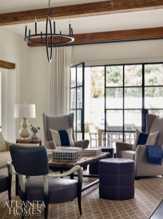 The family room boasts views of the home's sprawling backyard. The chandelier, wingback chairs, coffee table, rug and ottomans are from Stanton Home Furnishings. The faux horn chairs are Bernhardt.