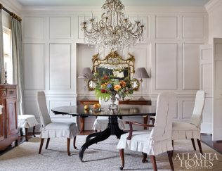 In the midst of exquisite crystal, gilt and antique case pieces, a Regency-style, black-lacquer dining table gives this room its solid center of gravity. Flowers by Holly Bryan Floral & Botanical Design.