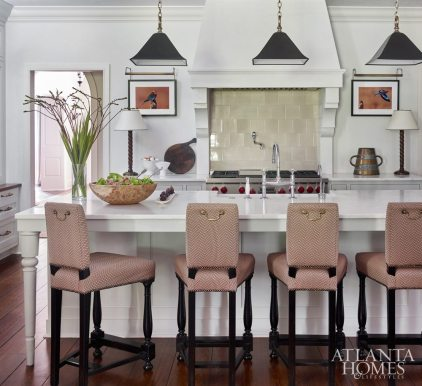 To coordinate with the rusty tone of the owner's avian photography, Bryan chose a chocolate brown herringbone for the McAlpine Home counter stools and updated them with unlaquered brass hardware.