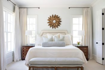 "The master bedroom includes a comfortable space to curl up with a book and take in the view outside. It's accented with botanical prints the homeowner picked up at Scott Antique Market. ""She favors neutrals and wanted the master bedroom to be an oasis of calm and relaxation,"" says Ghegan."