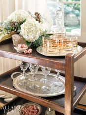 Silver trays, crystal and gold-rimmed glasses from Acquisitions add interest to the bar cart.