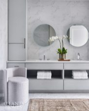 """Describing the before as """"brown and dark,"""" Wheeler reimagined the master bath as a fresh and airy space wrapped in Carrara marble from Stonelluxe. The vanity chair is by A. Rudin from Paul + and the rug is Moattar."""