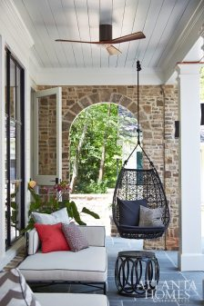 To create the feeling of a cohesive living space, Musso Design Group's color palette—along with a few bursts of chevron pattern—travels from the family room to the screened-in porch. Chaise longues on the loggia echo a daybed designed by Musso. Suspended from the ceiling, it is a modern nod to a porch swing but roomy enough to accommodate afternoon naps.