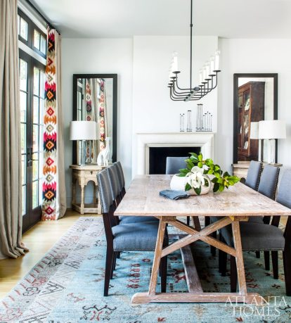 """""""This rug helped my client realize that she gravitates towards geometric prints, so you'll see that in other rooms as well,"""" says McFadden. Glamorous elements include a pair of antique tables and an elaborate embroidered textile."""