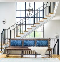 A long bench in a bright blue fabric accents the crown jewel of the house—a wrought iron center stairway with elegant arched detailing.