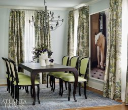 Formal furnishings strike a vivacious note in the dining room, where green-and-blue silk drapes by Jim Thompson and the homeowner's collection of antiques mix seamlessly with the contemporary polar bear print.
