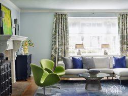 "Papadopoulos hesitates to use the term ""formal"" to describe the living room. While it's more traditional than the family room, she mixed modern furniture, like the Platner cocktail table and bright-green swan chairs, with antique chests and traditional Jim Thompson silk draperies to keep the space refined yet approachable."