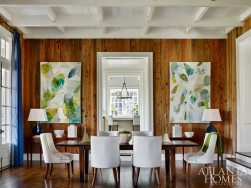 """With the home essentially built for hosting, Dixon gave special consideration to the flow of rooms. """"There's a great visual link from the kitchen all the way to the living room fireplace,"""" he says. """"While it feels connected, there's still a little formality and separation between spaces, so that it doesn't feel like the kitchen sink is right on top of you when entertaining."""" In the combination living/dining room, rustic pecky cypress walls are tempered with contemporary artwork by Elizabeth Barber."""