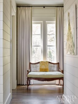 In the master bedroom hallway, a cane-back settee with pretty curves, one of the client's treasured pieces, was updated in a Pindler fabric and Samuel & Sons trim.