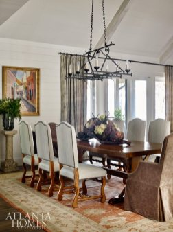 Classic Chic The stately dining area pairs high-back chairs from the client's collection with upholstered, skirted Edward Ferrell host chairs, which soften the space along with an Oushak rug. The sculptural basket is by Asheville, North Carolina, artist Matt Tommey.