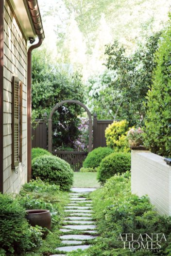 White hellebore, lavender mazus, ostrich fern, pachysandra and Southern shield fern fill a transition garden leading to a second garden gate.