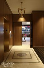 Suzanne Kasler—who holds a background in commercial design—collaborated with the architects of Mercedes-Benz Stadium to design a residential-like owner's suite for Arthur Blank. Directly off the elevator, a custom floor inlay greets guests as does a Christopher Boots fixture, available through R Hughes.