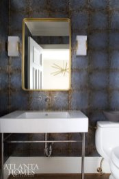 The powder room is wrapped in a lustrous blue mirrored wall covering from Zoffany, introducing a dose of drama and continuing the color story. The alabaster glass sconces are by Kelly Wearstler for Visual Comfort, while the brass-framed mirror reflects a midcentury-inspired chandelier beyond.