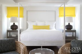 The master bedroom serves as a masterful example of the color-blocking Lee Kleinhelter has become celebrated for, achieved in this instance with sunshine yellow and luminous white. Basket-woven rattan armchairs demarcate the master sitting area, where a transparent Lucite table and creamy cowhide keep things light. In the understated adjoining bath, a curly Tibetan goat fur vanity stool provides softness and a visual break.
