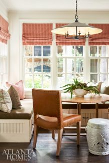 The breakfast nook features built-in seating along with leather chairs. Woodbery added pillows in a mix of patterns—an agate print and Swiss cross design—to enliven the space along with roman shades in a muted terra-cotta stripe by Carleton V. through Ainsworth-Noah.