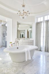 The oval-shaped master bath showcases recessed vanities, a freestanding Kohler tub through PDI and a chandelier by Visual Comfort, also through PDI.