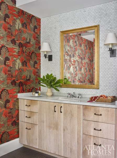 In the master bath, Osborne & Little's Summer Palace wallpaper gives a sense of gravitas as it meets a backdrop of tiny marble tiles.