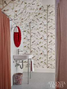 The bathroom gleans whimsy from a Schumacher wallpaper.