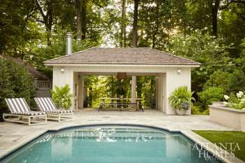 The tranquil outdoor oasis includes a pool house complete with a table by Skylar Morgan and a bench by Kendrick Anderson—both local woodworkers whom Square Feet Studio commissions often. Around the poolside, Janus et Cie loungers and a daybed upholstered in a weather-resistant Perennials stripe add a certain crispness that is countered by container plantings by Floralis Garden Design.