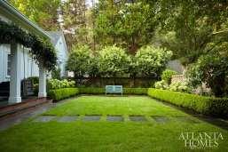 Annabelle hydrangeas and hedges of clipped American boxwood border an understated section of grass. At left, a custom swinging day bed is visible from the terrace.
