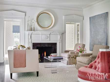 In this historic Atlanta home, modern touches such as a clean-lined Wesley Hall sofa and Lucite coffee table from Travis & Company offer a fresh perspective amid millwork dating back to the 1920s. The armchairs are by Mrs. Howard for Sherrill Furniture and the antique mirror is from Parc Monceau. The painting is by Mark Leibert, represented by Sandler Hudson Gallery.