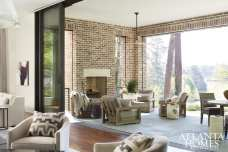 A NanaWall glass wall system opens up to create a sprawling indoor-outdoor space with magnificent vistas of the neighboring golf course. An electronic Lutron shade rolls down for privacy or insect control, while teak furnishings from Restoration Hardware and concrete stools from McGuire Furniture create a comfortable arrangement near the outdoor fireplace.