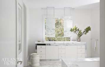 In the master bathroom, a pair of mirrors fabricated by Kevin Grisso of Custom Artisan Group have been suspended from the ceiling above a white vanity with chrome detailing.