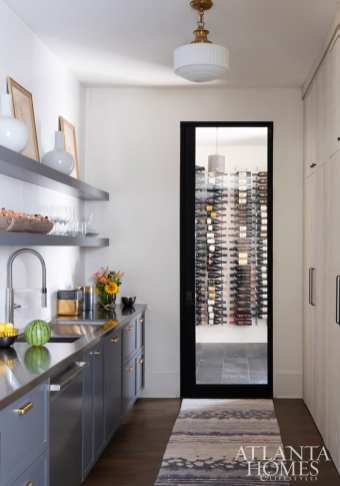 The butler's pantry corridor reveals both builder Siegel Construction & Design's astute finish selections—like steel-blue cabinets and antiqued brass—and its knack for lighting, like this vintage-inspired pendant in white glass. The climate-controlled wine cellar comes in handy for the homeowners, who enjoy collecting.