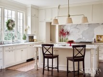 The Calacatta gold backsplash in the kitchen almost looks like an abstract painting, says designer Lynne T. Rankin. The oversize vent hood, cabinets and island are by Woodcrest. The light fixtures are custom by Eloise Pickard and the window looks out onto a boxwood garden.