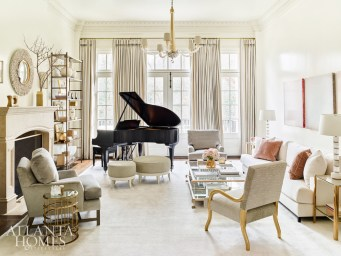 A soft rug and high-gloss paint create a bright, light backdrop for a custom sofa in silk velvet by Christian Liaigre, brass accent tables, a gilded chair and the owner's piano.