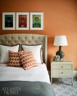 An orange accent wall and framed superhero prints add a jolt of energy to the son's bedroom.