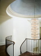 In the soaring entry foyer, a three-tiered crystal chandelier reflects light softly off of the metallic paint on the domed ceiling.