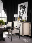 Vintage, abstract artwork rests on a striking sideboard by Andre Arbus with a parchment finish and forged iron columns. Wooden frame chairs by Robert Brown and upholstered Baker chairs surround the custom, 60-inch round table designed by Brown.
