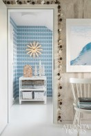 In the entry, Flynn and graphic designer Ashley Bothwell designed custom wallpaper in a pixelated version of classic Nordic sweater patterns. The white table is from Duralee, while the clock and baskets were found locally in Iceland.