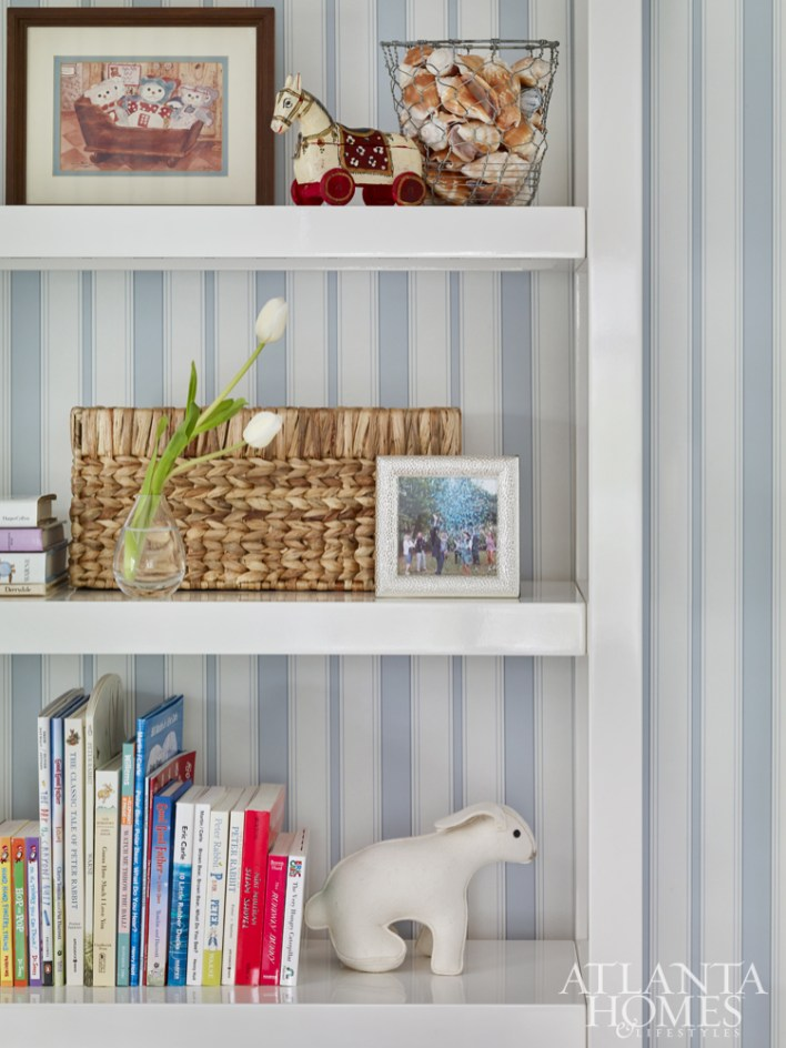 The clean lines of the bookshelves counteract the room's more traditional elements and offer a spot to display prized items like a print that was once in Lowe's own nursery as a child.