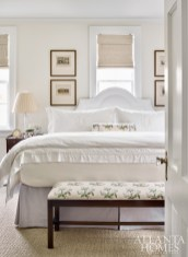 A pared down aesthetic in the master bedroom helps the small space live larger. Lowe repeated Colefax and Fowler's iconic Bowood floral chintz throughout the room.